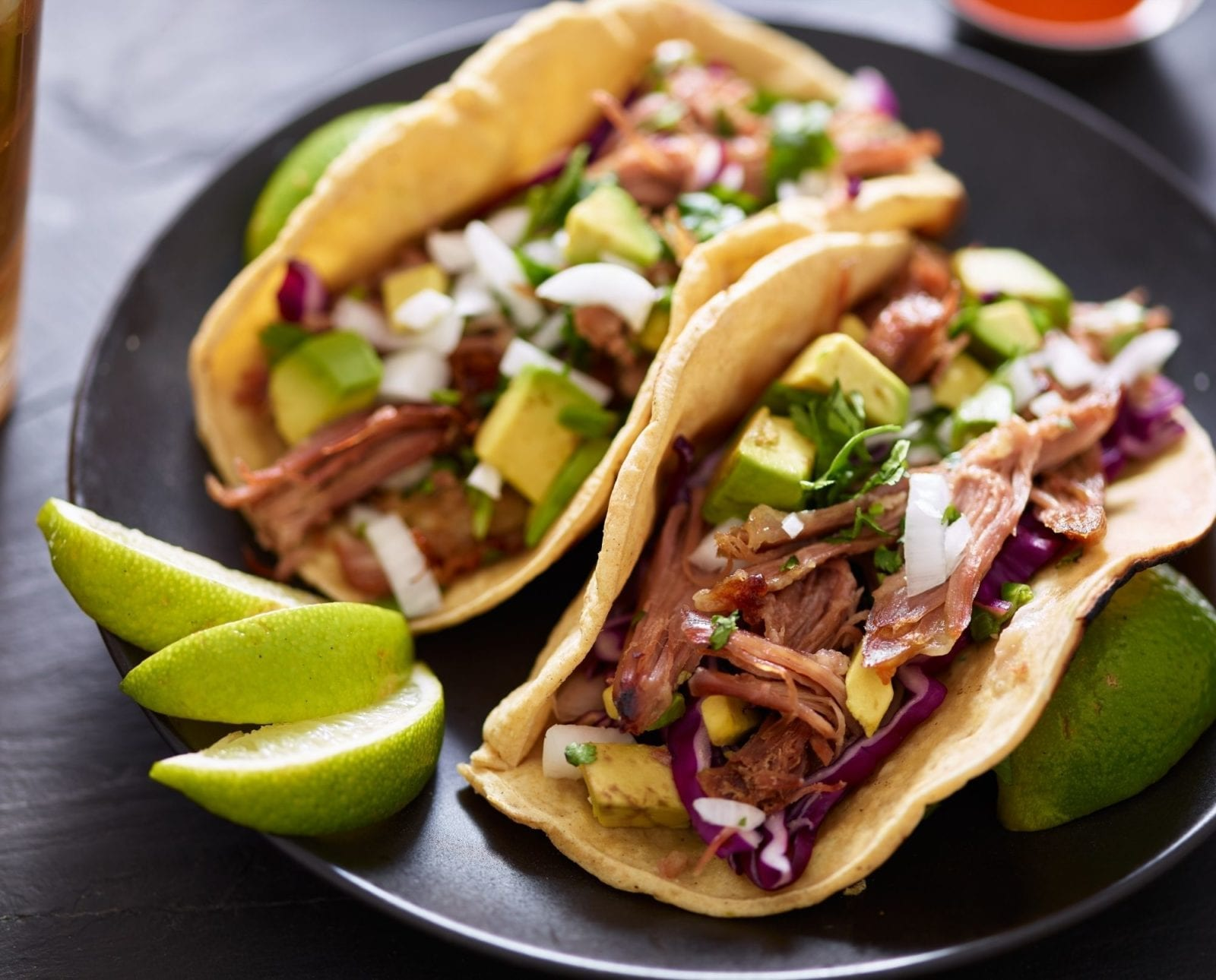 Meaty carnitas in flour tortillas with avocado, lime, and cilantro on a black plate.