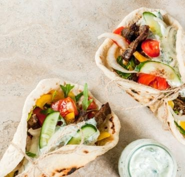 Two gyros folded up with meat, cucumbers, and tomatoes spilling out. There is dipping sauce on the side on a plain counter.