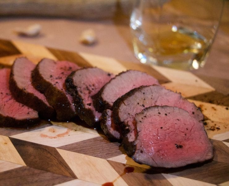 Medium-rare venison backstrap on a checkerboard wooden cutting board with whiskey on the side. There is an antler and elk ivories in the background.
